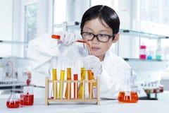 Kleiner Wissenschaftler, der Experiment im Labor macht stockfoto