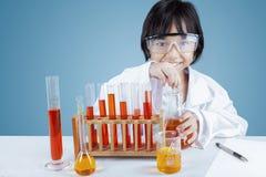 Kleiner Wissenschaftler, der Experiment tut stockfotos