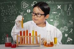 Kleiner Wissenschaftler mit Chemikalie im Labor Lizenzfreies Stockbild