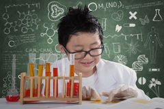 Kleiner Wissenschaftler schafft chemische Tests lizenzfreie stockfotografie