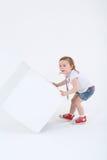 Kleines überraschtes Mädchen mit Medaille auf Kasten hebt Würfel auf Stockbilder