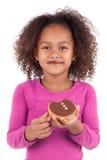 Kleines afrikanisches asiatisches Mädchen, das einen Schokoladenkuchen isst Stockfoto