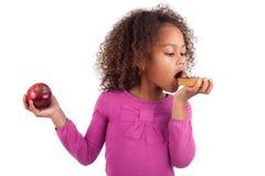 Kleines afrikanisches asiatisches Mädchen, das einen Schokoladenkuchen isst Stockfotos