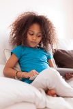 Kleines afrikanisches asiatisches Mädchen, das einen Tablette-PC verwendet Lizenzfreie Stockfotos