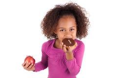 Kleines afrikanisches asiatisches Mädchen, das einen Schokoladenkuchen isst Stockbild