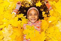 Kleines afrikanisches Mädchen bedeckt mit Ahornblättern Stockbilder
