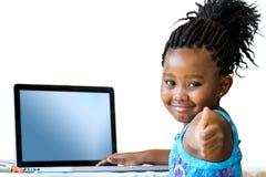 Kleines afrikanisches Mädchen, das oben Daumen am Schreibtisch tut Lizenzfreie Stockfotografie