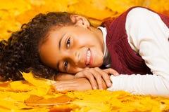 Kleines afrikanisches Mädchen legt auf Herbstgelbblätter Lizenzfreie Stockfotos