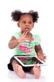 Kleines Afroamerikanermädchen, das einen Tablette-PC verwendet Lizenzfreie Stockbilder