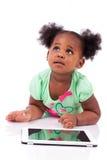 Kleines Afroamerikanermädchen, das einen Tablette-PC verwendet Stockbilder