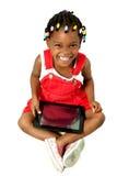 Kleines Afroamerikanermädchen, das einen Tablette-PC verwendet Stockbild