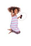 Kleines Afroamerikanermädchen, das Musik - Querstation springt und hört Lizenzfreies Stockfoto