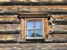 Kleines altes Fenster mit Glas mit einem blauen Himmel auf dem Hintergrund der hölzernen Wand des Landschaftsblockhauses Stockfotografie