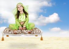 Kleines arabisches Mädchen, das auf Flugwesenteppich sitzt Lizenzfreie Stockfotografie