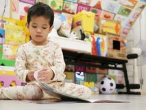 Kleines asiatisches Baby, das ein Buch öffnet und erforscht stockfoto