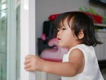 Kleines asiatisches Baby, das lernt, durch zu schließen/nahe Schiebetür stockfotografie