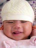 Kleines asiatisches Baby, das schüchtern gluckst Lizenzfreies Stockfoto