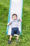 Kleines asiatisches Kind, das Dia am Spielplatz spielt Stockfoto