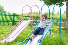 Kleines asiatisches Kind, das Dia am Spielplatz spielt Lizenzfreies Stockbild