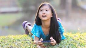 Kleines asiatisches Kind, das Spiel am intelligenten Telefon spielt stock footage