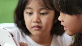 Kleines asiatisches Kinderaufpassende Tablette im Park zusammen auf grünem Schirm stock video