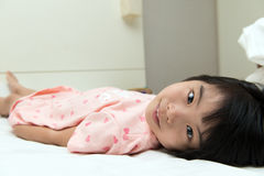 Kleines asiatisches Mädchen auf Bett Stockfotografie