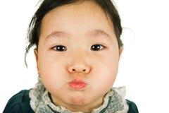 Kleines asiatisches Mädchen bläst Backen auf Stockfoto