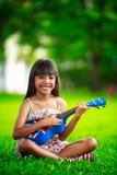 Kleines asiatisches Mädchen, das auf Gras und Spielukulele sitzt Stockfoto