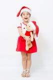 Kleines asiatisches Mädchen, das Bärnpuppe auf Weihnachten umarmt Stockfotos
