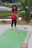 Kleines asiatisches Mädchen, das Golf spielt Stockbild