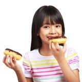 Kleines asiatisches Mädchen, das Schokoladenschaumgummiringe hält und isst Lizenzfreie Stockfotos