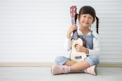 kleines asiatisches Mädchen, das Ukulele spielend auf weißem Hintergrund mit Kopienraum sitzt lizenzfreies stockfoto