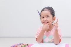Kleines asiatisches Mädchen des Lächelns mit Bleistiftfarbe auf weißem Hintergrund Lizenzfreies Stockbild