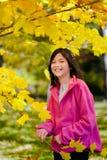Kleines asiatisches Mädchen durch Herbstlaub Stockbilder