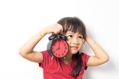 Kleines asiatisches Mädchen ist am Wecker für sie oben aufwecken verärgert stockfoto