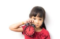 Kleines asiatisches Mädchen ist am Wecker für sie oben aufwecken verärgert lizenzfreies stockbild