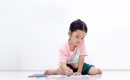 Kleines asiatisches Mädchen mit Bleistiftfarbe auf weißem Hintergrund Lizenzfreie Stockfotos