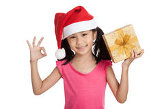 Kleines asiatisches Mädchen mit Sankt-Hut und Geschenkbox stellen O.K. dar Lizenzfreie Stockfotografie