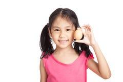 Kleines asiatisches Mädchenlächeln mit einem Ei in der Hand lizenzfreies stockfoto