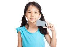 Kleines asiatisches Mädchenlächeln mit einer leeren grauen Karte lizenzfreie stockbilder