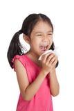 Kleines asiatisches Mädchenniesen mit Serviettenpapier Stockbild