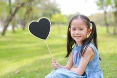 Kleines asiatisches M?dchen Smilling, das den leeren Herzaufkleber liegt auf gr?nem Gras am Sommergarten h?lt lizenzfreie stockbilder