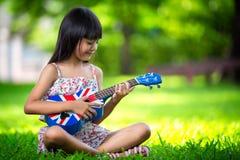 Kleines asiatisches Mädchen, das auf Gras und Spielukulele sitzt Stockbild