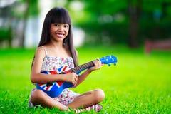 Kleines asiatisches Mädchen, das auf Gras und Spielukulele sitzt Stockbilder