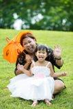 Kleines asiatisches Mädchen, das auf grünem Gras mit ihrer Mutter spielt Stockfotografie