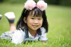 Kleines asiatisches Mädchen, das auf grünem Gras am Park spielt Lizenzfreie Stockbilder