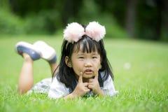 Kleines asiatisches Mädchen, das auf grünem Gras am Park spielt Lizenzfreies Stockbild