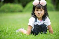 Kleines asiatisches Mädchen, das auf grünem Gras am Park spielt Stockfoto