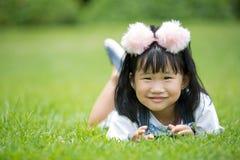 Kleines asiatisches Mädchen, das auf grünem Gras am Park spielt Stockfotos