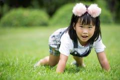 Kleines asiatisches Mädchen, das auf grünem Gras am Park spielt Stockbild